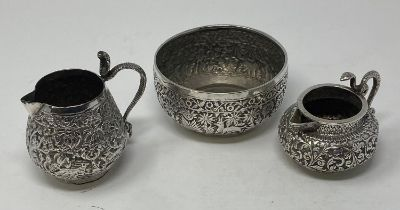 An Indian silver coloured metal cream jug, with a Cobra snake handle, 8 cm high, another similar,