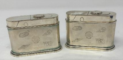 A pair of plated table top cigarette lighters, decorated shells, 9 cm wide 6 cm high