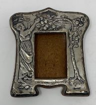 An early 20th century silver mounted strut photograph frame, embossed a lady picking apples,