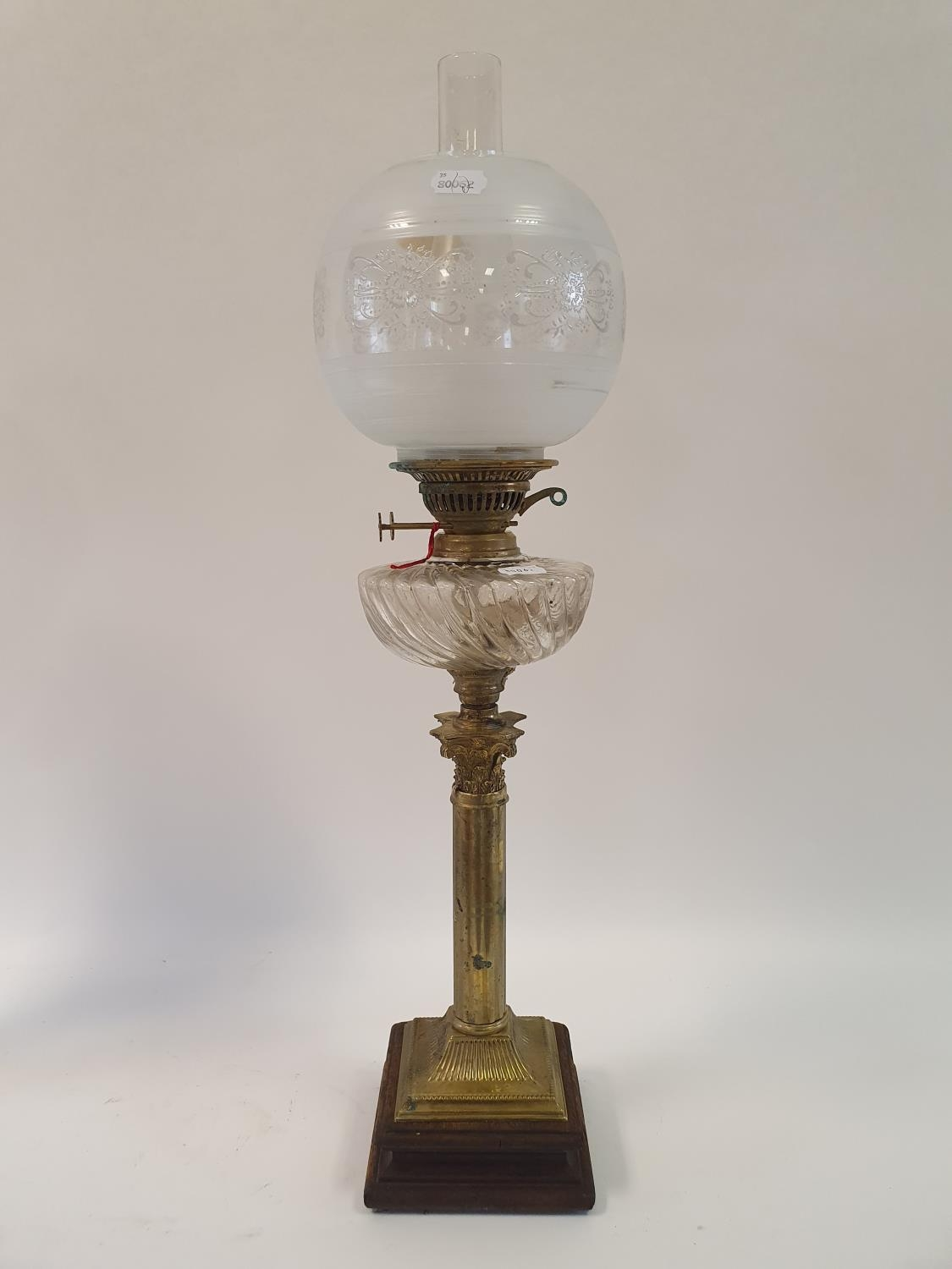 An oil lamp, with an acid etched glass shade, a clear glass well, on a brass base in the form of a
