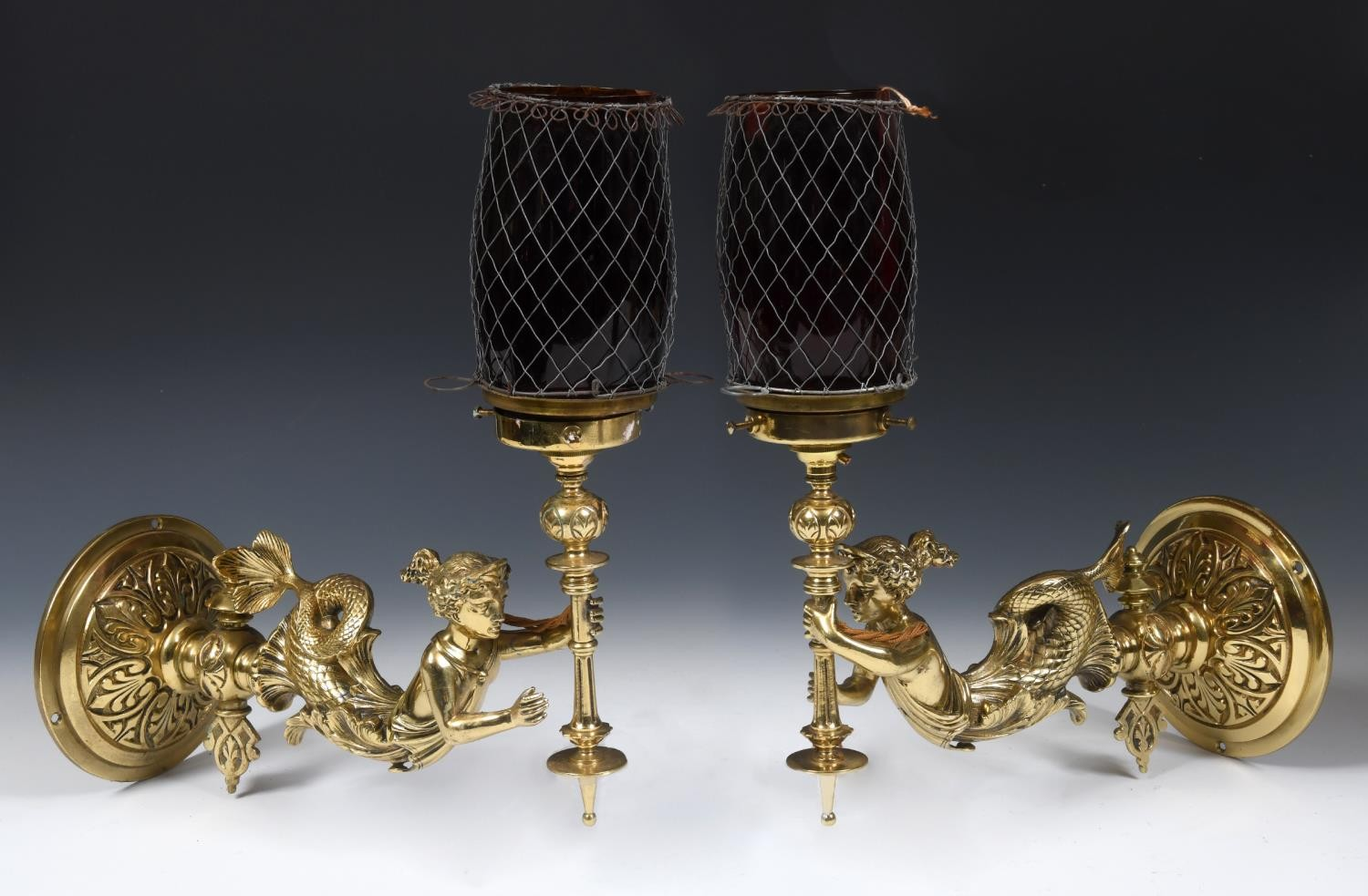 A pair of late 19th/early 20th century brass gas lamps, in the form of mermaids holding torches,