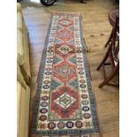 A Persian type red ground runner multiple borders centre with repeating lozenge shape medallions,