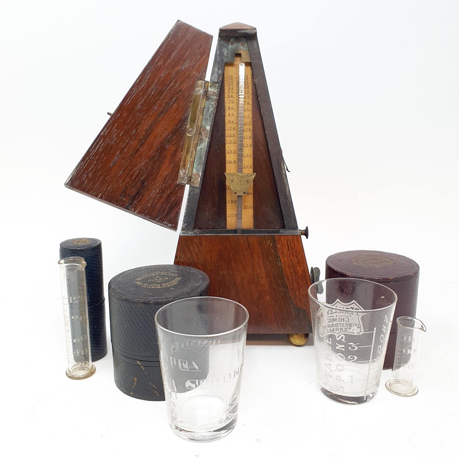 An early 20th century metronome, in a rosewood case, nine glass measures in leather cases and