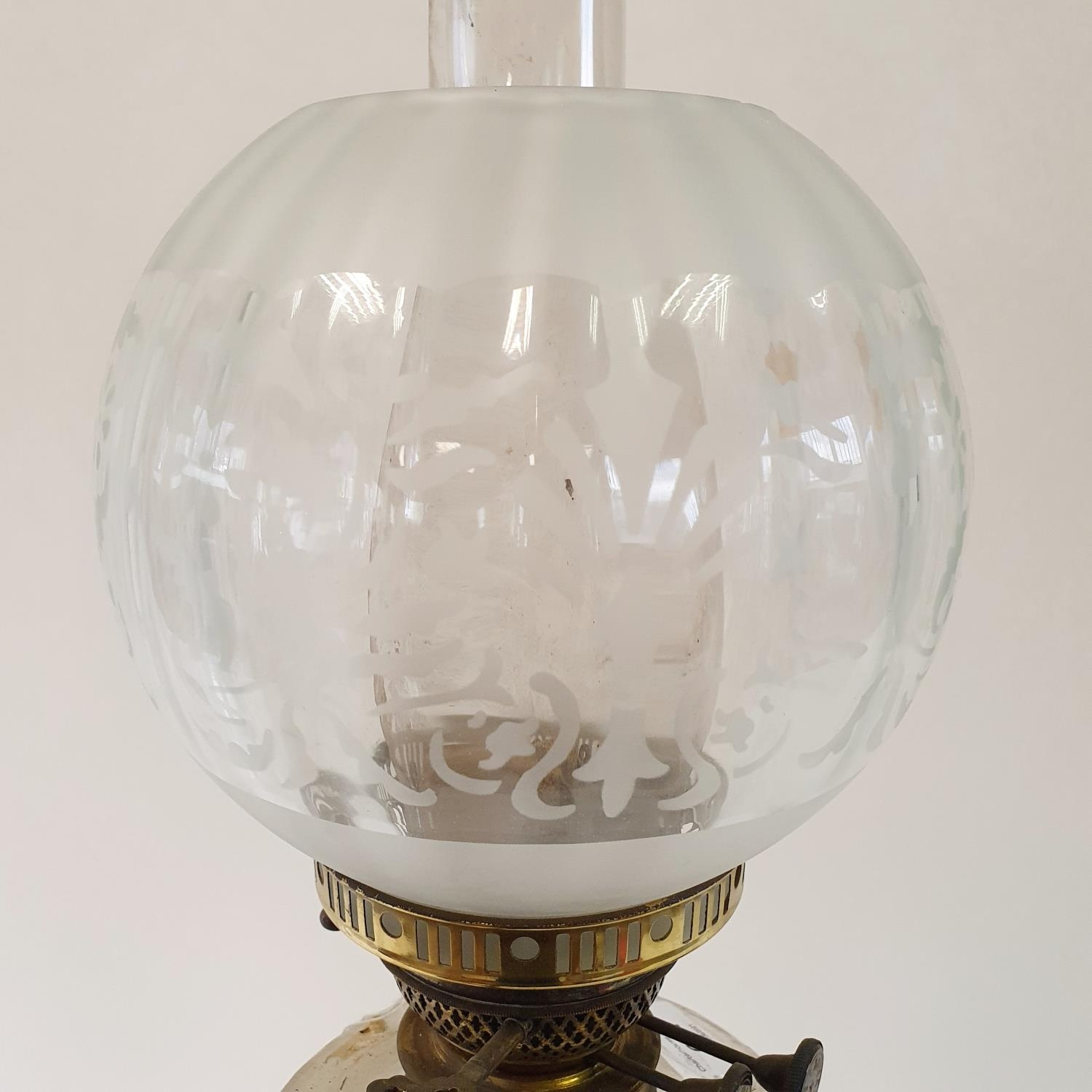 An oil lamp, with an acid etched glass shade, a clear glass well on a brass base in the form of a - Image 4 of 4