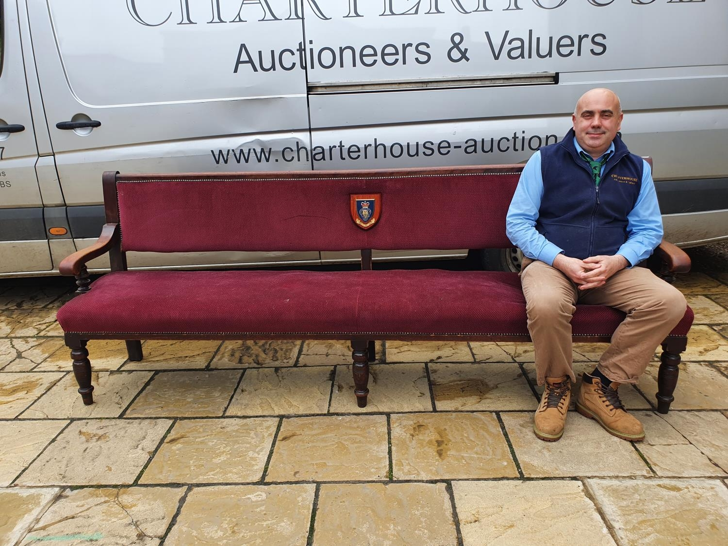 A mahogany settle, with upholstered back and seat, back inset with plaque for the Royal British