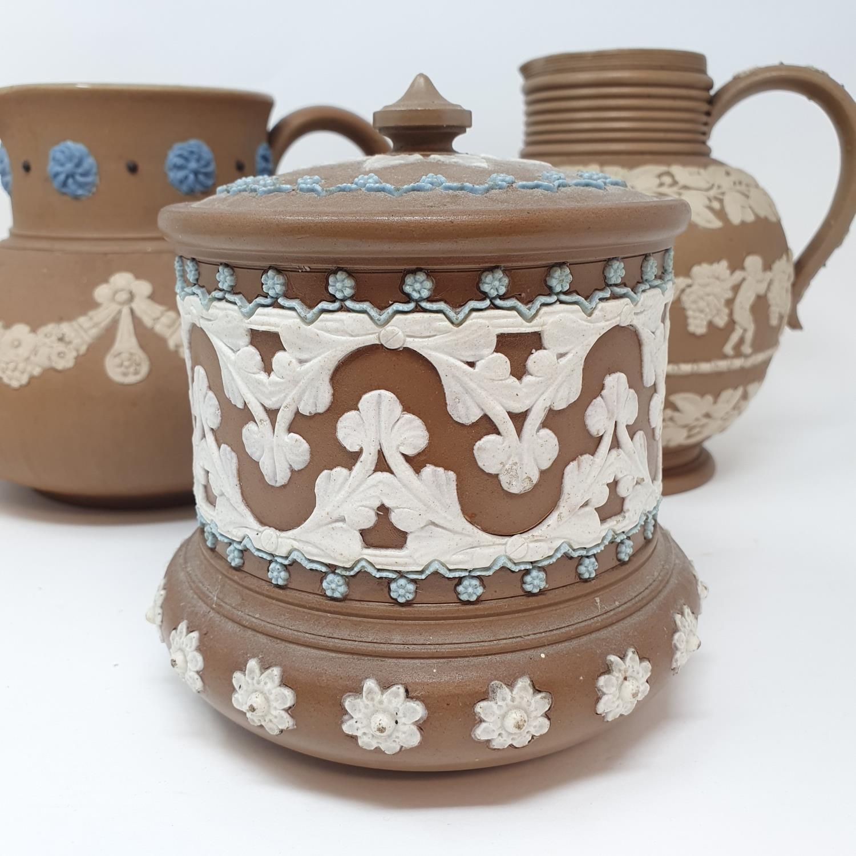 A Doulton Lambeth tobacco jar, 15 cm high, and two Doutlon Lambeth jugs (3)