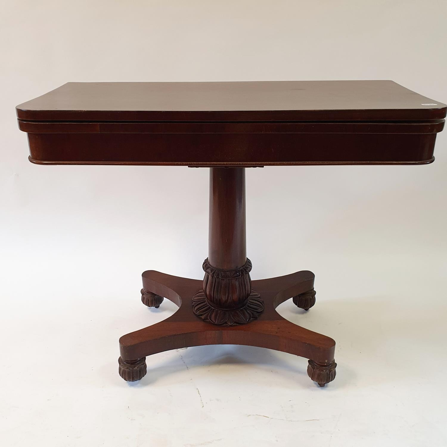 A mahogany plum pudding folding card table, on carved column support to shaped base on carved bun