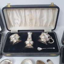 A silver three piece cruet, boxed, an egg cup and spoon, boxed, a napkin ring, boxed, a glass