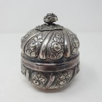 A Continental silver colour metal box, decorated flowers, 9 cm diameter 6.9 ozt, untested