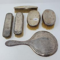 An Edward VII silver backed mirror, five silver backed brushes, and four photograph frames,