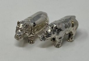 A silver hippo and a rhino (2) This is a modern copy Untested silver coloured metal,