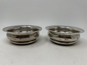 A pair of silver and mahogany bottle coasters, 12.5 cm diameter (2) Marks rubbed