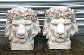 A pair of distressed painted urns in the form of lion heads, each 43cms (17ins) high (2).