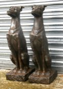 A pair of faux stone (fibreglass) garden figures in the form of seated dogs, 79cms (31ins) high.
