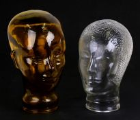 An amber glass mannikin head; together with another similar in the Art Deco style, the largest 28cms