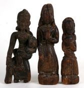 A group of three early carved wooden Asian figures, the largest 20cms (8ins) high (3).