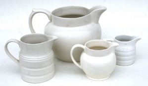 A group of four cream glazed jugs, the largest 23cms (9ins) high.