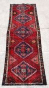 A Persian Azari runner with five geometric guls on a red ground, 297 by 101cms (117 by 40ins).