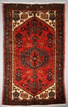 A Persian Hamadan hand knotted woollen rug with stylised design within borders, on a red ground, 159