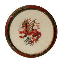 A circular needlework panel depicting a dragon, framed and glazed. 34cm (13.25 ins ) diameter