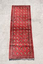 A Persian Balouch woollen hand knotted runner with repeat design on a red ground, 193 by 67cms (76