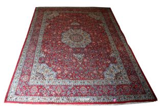 A Persian Mashad hand knotted woollen carpet with central floral medallion within foliate borders,