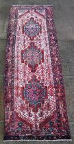 A Persian Hamedan woollen hand knotted runner with three repeated guls within stylised borders on