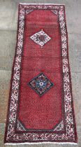 A Persian Hamadan hand knotted woollen runner with two central diamond motifs within a stylised