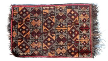 A small Persian rug decorated with geometric designs, 58 by 40cms (22.75 by 15.75ins).