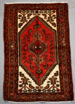 A Persian Hamadan hand knotted woollen rug with stylised central medallion within borders, 103 by
