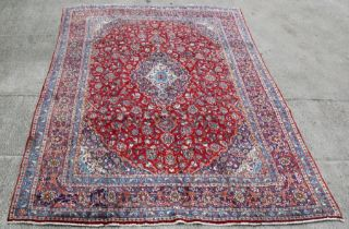 A Persian Mashad woollen hand knotted carpet with central floral medallion within floral borders
