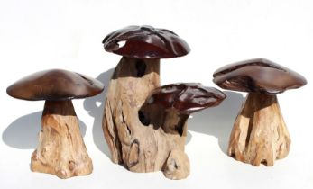 A group of three carved rootwood garden mushrooms, the largest 43cms (17ins) high (3).