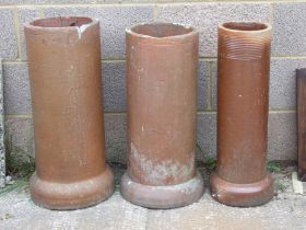 Three terracotta chimney pots / planters, the largest 69cms (27ins) high (3).