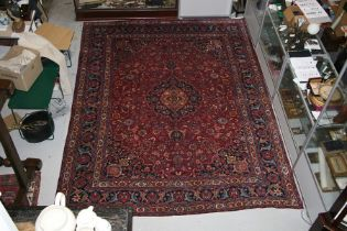 A Persian Kashan hand knotted woollen carpet with central floral gul within floral borders, on a red