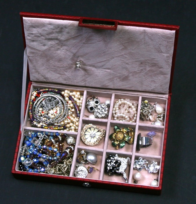 A red leather jewellery box containing assorted costume jewellery.