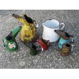 A Bluecol Anti-Freeze quart jug, a Castrol quart jug, an oil jug and other oil jugs.