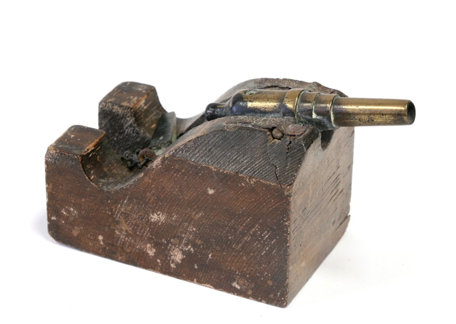 A desktop cannon with brass barrel, mounted on a wooden base, overall 13cms (5ins) long.