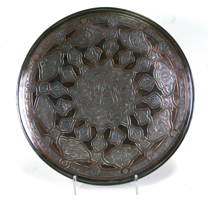 A large Islamic copper charger with white metal decoration including central Islamic script within