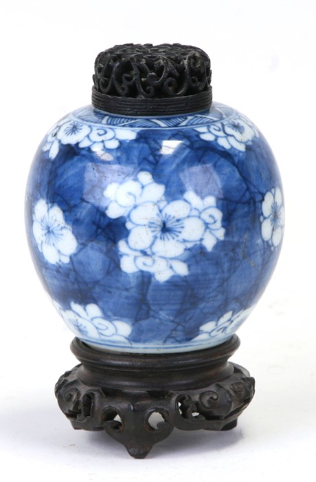 A Chinese blue & white ginger jar of small proportions decorated with prunus, with pierced wooden