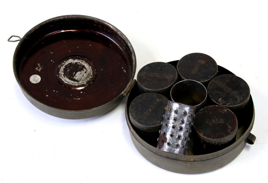 A tin spice box containing five spice jars and a grater, 15cms (6ins) diameter.