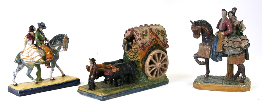 A Spanish pottery group depicting an ox cart, 31cms (12.75ins) long; together with two similar