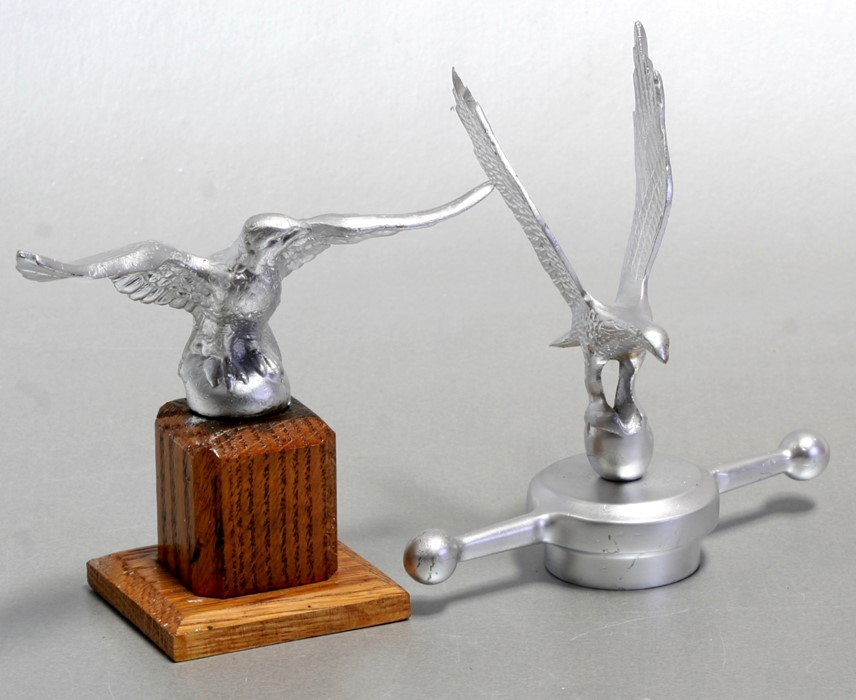 An accessory car mascot in the form of an eagle standing on an orb, mounted on a t-bar radiator cap,