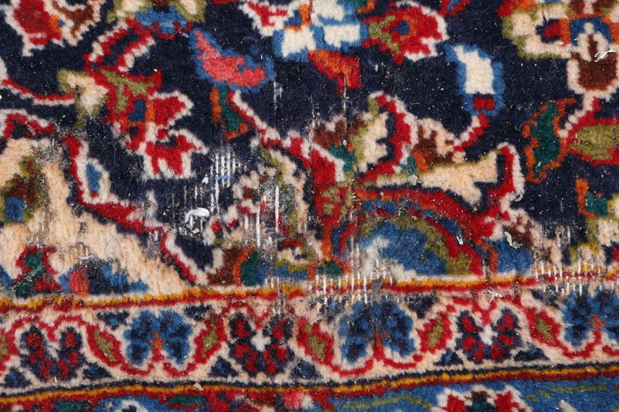 A Persian carpet with central floral medallion on a red ground within a multi floral border, 390 - Image 4 of 5