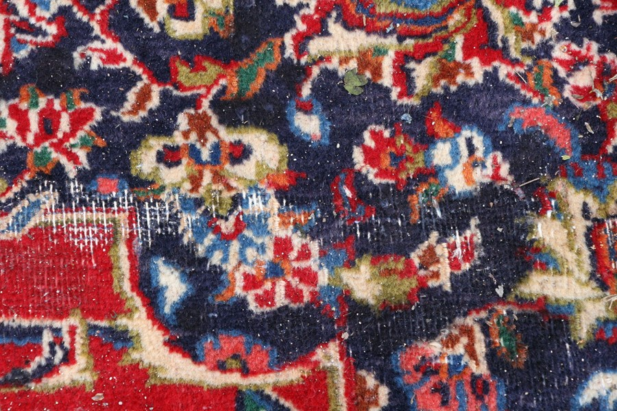 A Persian carpet with central floral medallion on a red ground within a multi floral border, 390 - Image 5 of 5