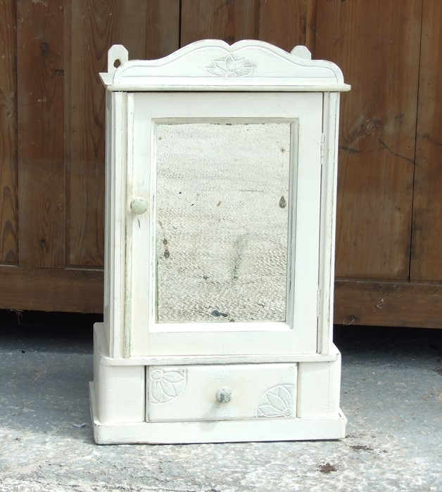 A distressed painted wall cupboard, the mirrored door above a single drawer, 36cms (14ins) wide.