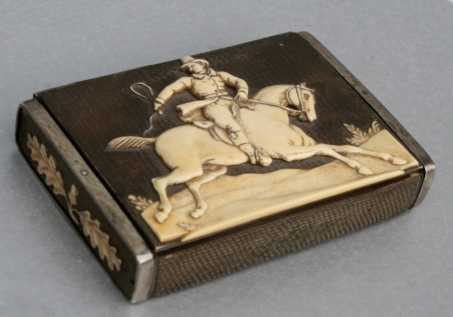 A 19th century German white metal mounted antler horn snuff box, the top carved with a gentleman