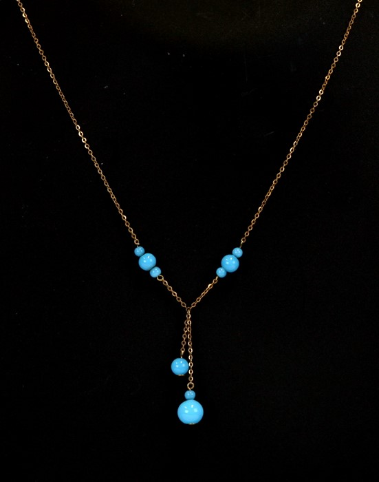 A 9ct gold necklace with turquoise coloured glass bead drops.