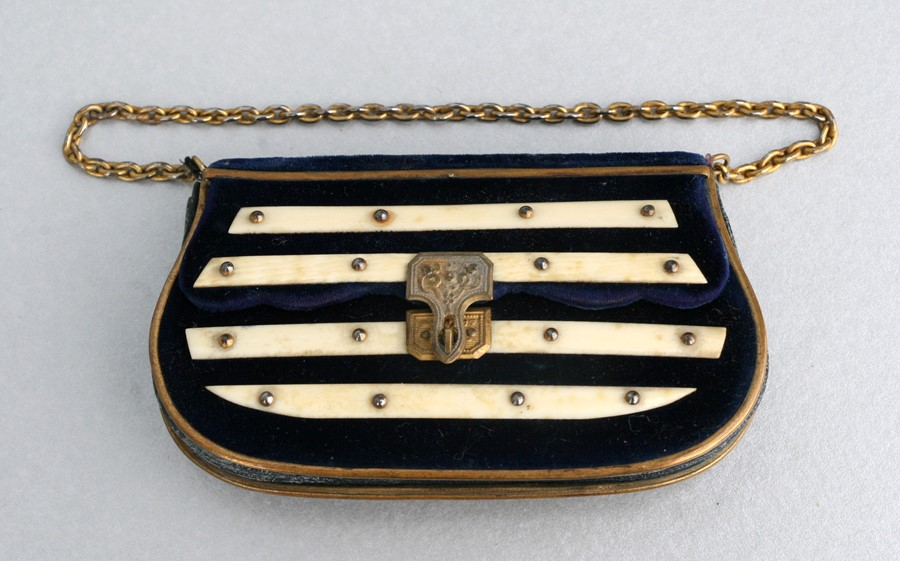 A 19th century gilt metal and ivory mounted velvet leather lined coin purse, 10cms (4ins) wide.