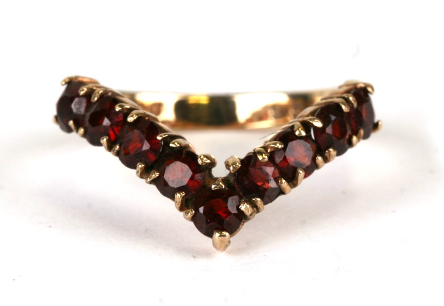 A 9ct gold wishbone ring set with red stones, possibly garnets, weight 2.6g, approx UK size 'L'