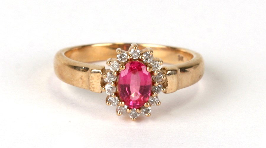 A 9ct gold cluster ring set with an oval pink stone surrounded by diamonds, weight 3.5g, approx UK